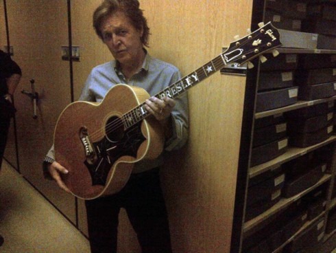 Paul McCartney holding Elvis' guitar at Graceland